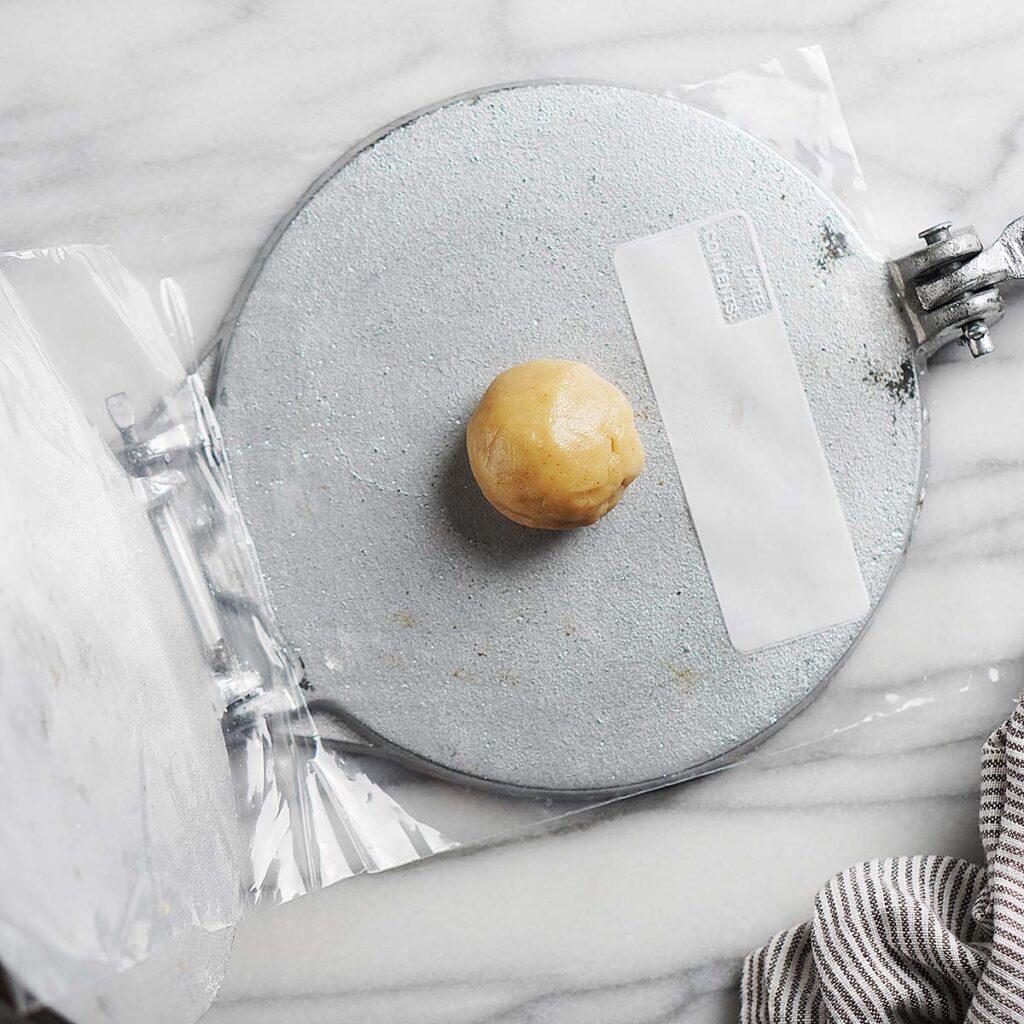 A dough ball inside a tortilla press lined with a sandwich bag.