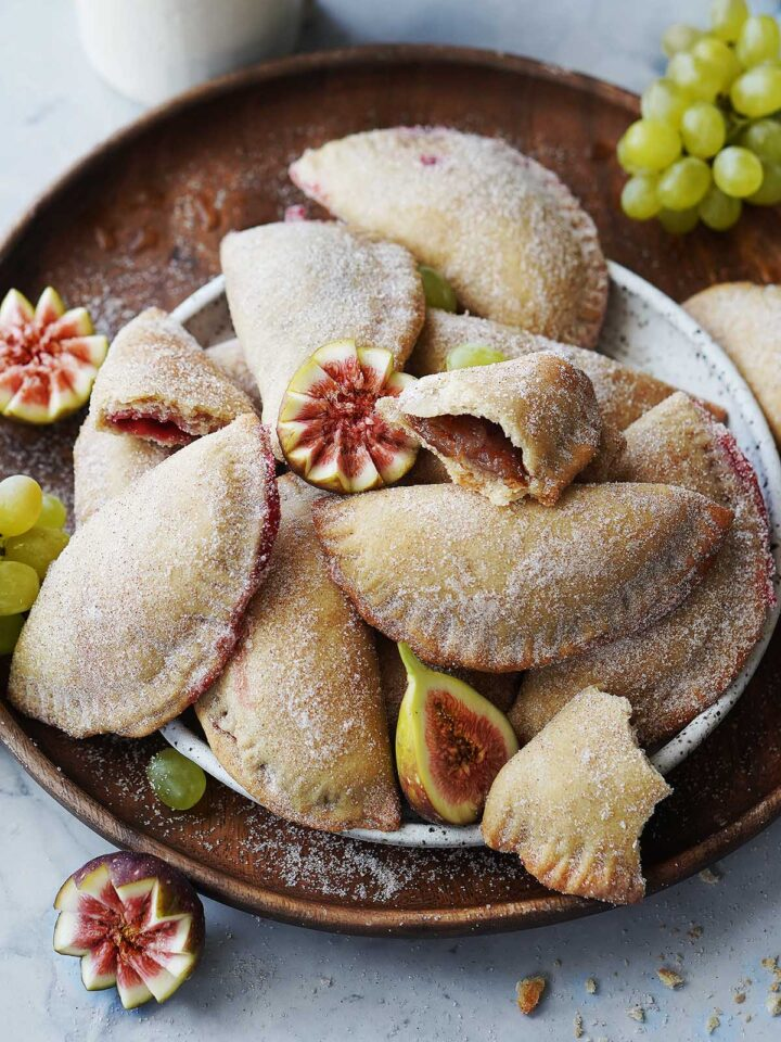 Crispy sweet empanadas on a white plate placed on a wood serving tray.
