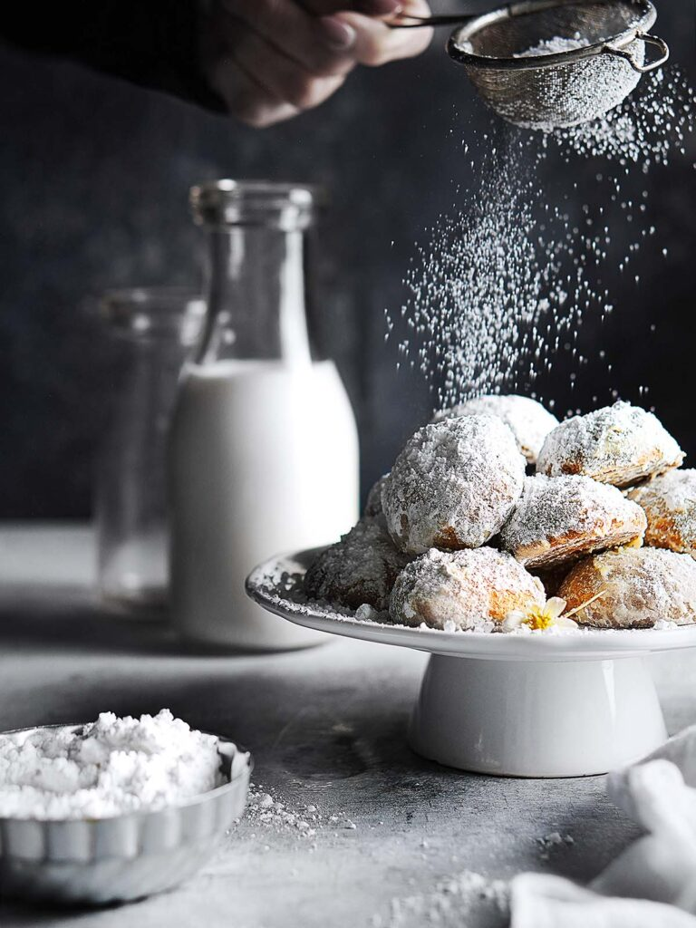Mexican Wedding Cookies placed on a small cake stand with a hand sprinkling sugar.